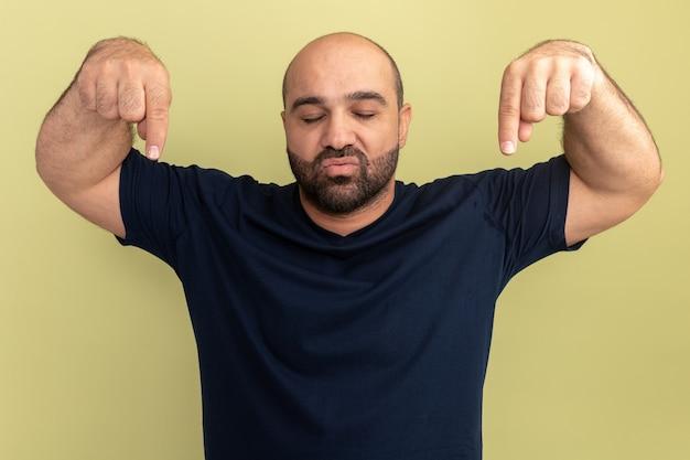 Brodaty mężczyzna w czarnej koszulce z zamkniętymi oczami z pewnym siebie wyrazem, wskazujący palcami wskazującymi w dół, stojący nad zieloną ścianą