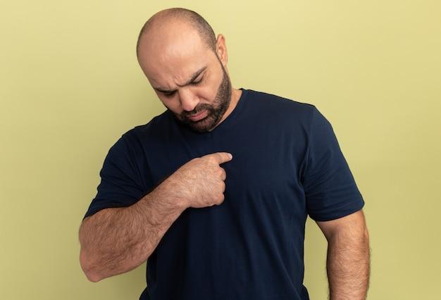 Brodaty mężczyzna w czarnej koszulce, zdezorientowany, wskazując palcem wskazującym na siebie stojącego nad zieloną ścianą