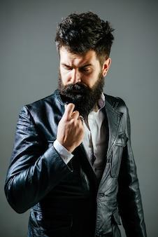 Brodaty mężczyzna w czarnej kurtce zamyślony mężczyzna w skórzanej kurtce fryzjerskiej koncepcja mody modnej