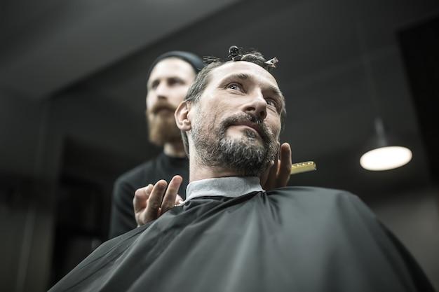 Brodaty mężczyzna w czarnej pelerynie do cięcia włosów w salonie fryzjerskim. na głowie ma spinki do włosów