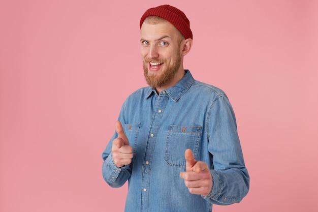 Brodaty mężczyzna w czerwonej czapce z modnej dżinsowej koszuli, zachęca, uśmiecha się, wykonuje gest wsparcia, wskazując w przód