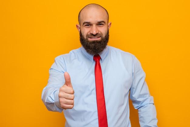Brodaty mężczyzna w czerwonym krawacie i koszuli wygląda na uśmiechniętego pewnie pokazującego kciuk w górę