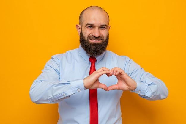 Brodaty mężczyzna w czerwonym krawacie i koszuli wyglądający, wykonując gest serca palcami uśmiechający się przyjaźnie