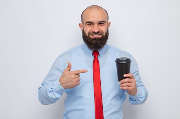 Brodaty mężczyzna w czerwonym krawacie i niebieskiej koszuli trzymający filiżankę kawy wskazującą palcem wskazującym, uśmiechający się pewny siebie, szczęśliwy i pozytywny