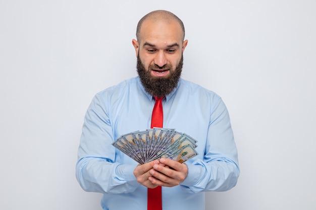 Brodaty mężczyzna w czerwonym krawacie i niebieskiej koszuli, trzymający gotówkę, patrzący na pieniądze zdumiony i zaskoczony uśmiechem