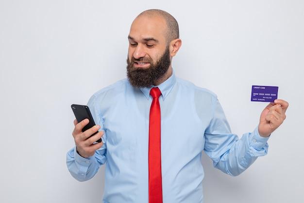 Brodaty mężczyzna w czerwonym krawacie i niebieskiej koszuli, trzymający kartę kredytową i smartfona, patrzący na nią szczęśliwy i podekscytowany