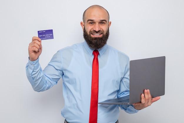 Brodaty mężczyzna w czerwonym krawacie i niebieskiej koszuli, trzymający laptopa i kartę kredytową, patrzący uśmiechnięty radośnie, szczęśliwy i pozytywny