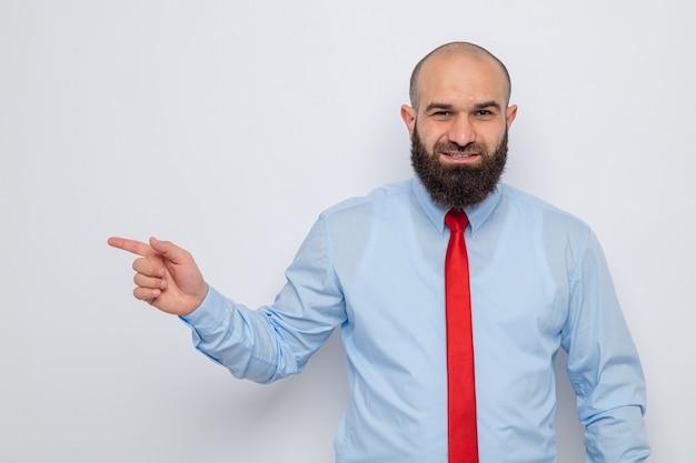 Brodaty mężczyzna w czerwonym krawacie i niebieskiej koszuli, uśmiechający się radośnie, wskazując palcem wskazującym w bok