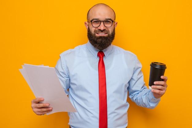 Brodaty mężczyzna w czerwonym krawacie i niebieskiej koszuli w okularach, trzymający dokumenty i filiżankę kawy, uśmiechający się radośnie smiling