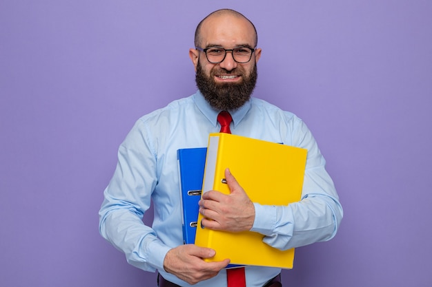 Brodaty mężczyzna w czerwonym krawacie i niebieskiej koszuli w okularach, trzymający foldery biurowe, patrzący w kamerę, uśmiechający się radośnie, stojący na fioletowym tle