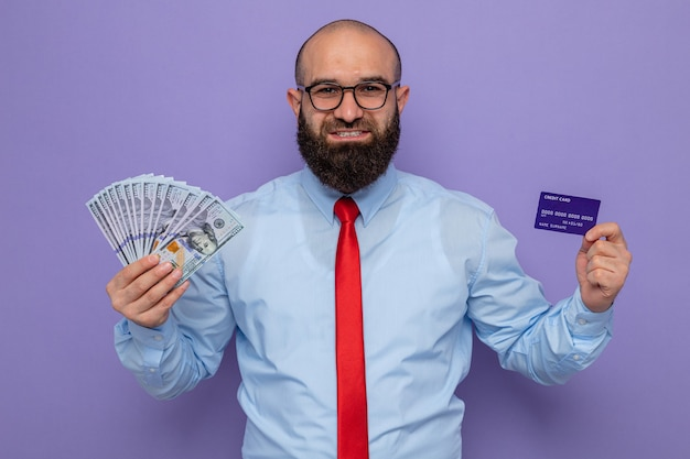 Brodaty mężczyzna w czerwonym krawacie i niebieskiej koszuli w okularach, trzymający gotówkę i kartę kredytową, wyglądający pewnie uśmiechnięty smiling