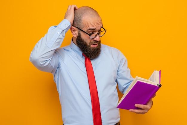 Brodaty mężczyzna w czerwonym krawacie i niebieskiej koszuli w okularach, trzymający książkę, patrząc na nią zdziwiony, drapiąc się po głowie stojąc na pomarańczowym tle