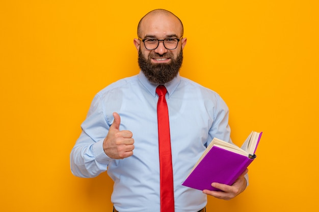 Brodaty mężczyzna w czerwonym krawacie i niebieskiej koszuli w okularach, trzymający książkę, patrzący w kamerę, uśmiechający się radośnie pokazując kciuk do góry stojący na pomarańczowym tle