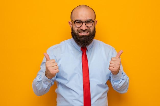 Brodaty mężczyzna w czerwonym krawacie i niebieskiej koszuli w okularach wygląda na szczęśliwego i podekscytowanego pokazując kciuk do góry