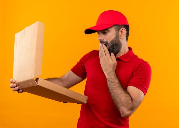 Brodaty mężczyzna w czerwonym mundurze i czapce trzyma otwarte pudełko po pizzy, patrząc na nie zaskoczony, stojąc nad pomarańczową ścianą