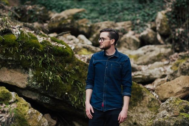 Brodaty mężczyzna w dzikim lesie z kamieniami dookoła