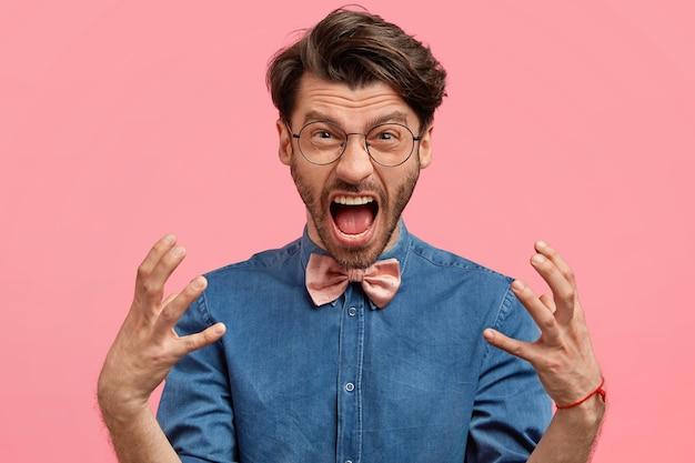 Brodaty mężczyzna w dżinsowej koszuli i różowej muszce