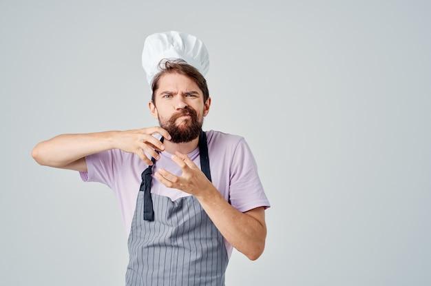 Brodaty mężczyzna w fartuchu kucharz gotuje w restauracji