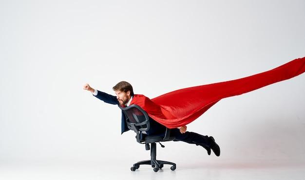 Brodaty mężczyzna w garniturze jeździ na krześle, czerwona peleryna supermana