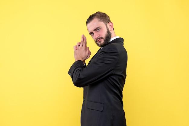Brodaty mężczyzna w garniturze pokazuje pistolet na palec