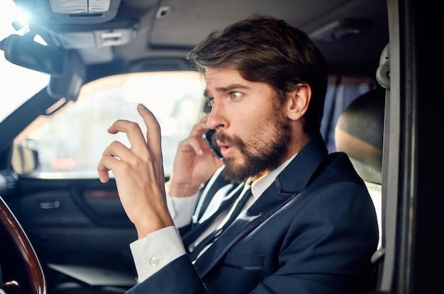Brodaty mężczyzna w garniturze w samochodzie podróż do pracy komunikacja przez telefon