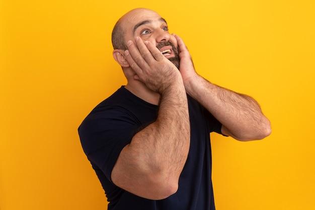 Brodaty mężczyzna w granatowej koszulce patrzy w górę zdumiony i zaskoczony, stojąc nad pomarańczową ścianą z rękami na twarzy