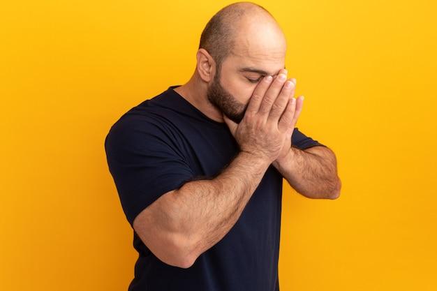 Brodaty mężczyzna w granatowej koszulce trzymający ręce razem na twarzy, przygnębiony i zmartwiony, stojący nad pomarańczową ścianą