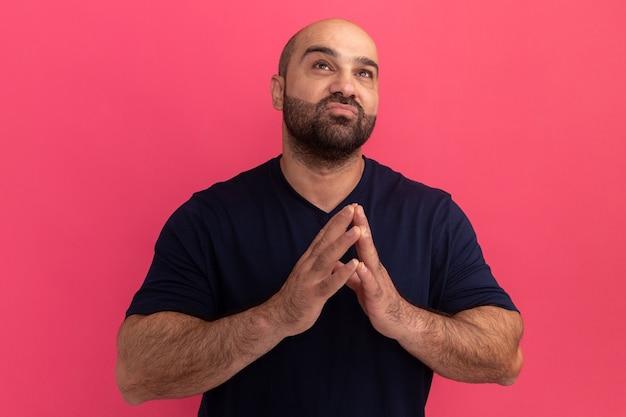Brodaty mężczyzna w granatowej koszulce trzymający się za ręce, jak modląc się, patrząc w górę z nadzieją stojącą nad różową ścianą
