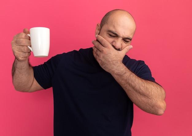 Brodaty mężczyzna w granatowej koszulce trzymający zmęczony kubek zakrywający usta ręką stojącą nad różową ścianą