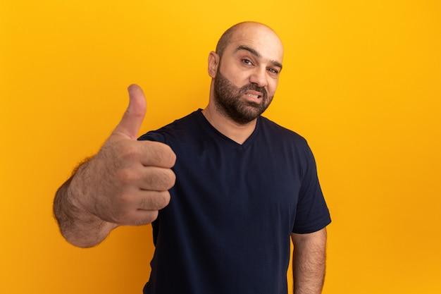 Brodaty mężczyzna w granatowej koszulce uśmiechnięty pokazując kciuki do góry stojąc na pomarańczowej ścianie