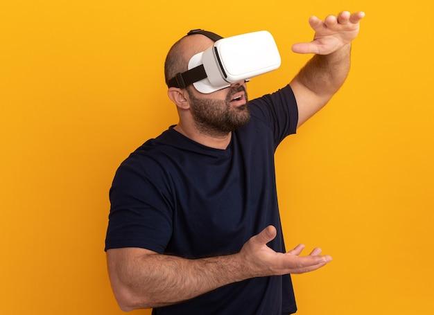Brodaty mężczyzna w granatowej koszulce w okularach wirtualnej rzeczywistości, gestykuluje rękami stojącymi na pomarańczowej ścianie