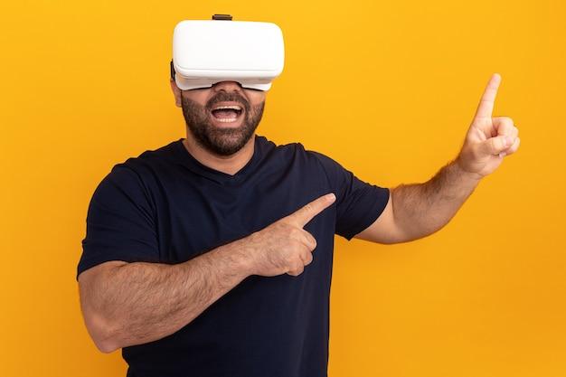 Brodaty mężczyzna w granatowej koszulce w okularach wirtualnej rzeczywistości wskazujący palcami wskazującymi w bok stojący nad pomarańczową ścianą