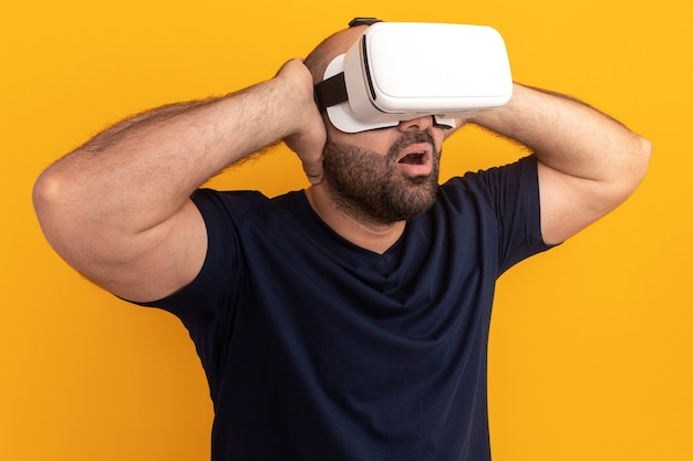 Brodaty mężczyzna w granatowej koszulce w okularach wirtualnej rzeczywistości wygląda na zdumionego i zaskoczonego stojącego nad pomarańczową ścianą