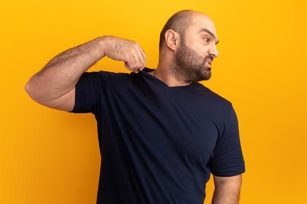 Brodaty mężczyzna w granatowej koszulce wyglądający na zirytowanego i poirytowanego dotykającego swojej koszulki stojącej nad pomarańczową ścianą
