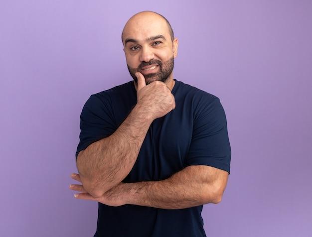 Brodaty mężczyzna w granatowej koszulce z ręką na ching uśmiechnięty pewny siebie stojący nad fioletową ścianą