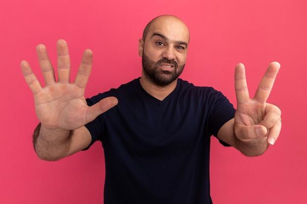 Brodaty mężczyzna w granatowej koszulce z uśmiechem na twarzy przedstawiający numer siedem stojący nad różową ścianą