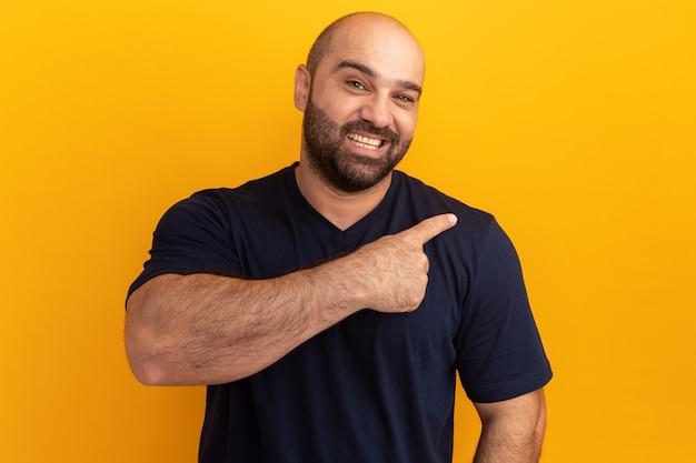 Brodaty mężczyzna w granatowej koszulce z uśmiechem na twarzy wskazujący palcem wskazującym w bok stojący nad pomarańczową ścianą