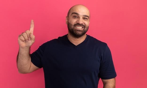 Brodaty mężczyzna w granatowej koszulce z wielkim uśmiechem na twarzy pokazuje palec wskazujący stojący nad różową ścianą