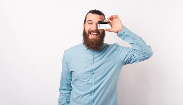 Brodaty mężczyzna w jasnoniebieskiej koszuli zasłania jedno oko kartą kredytową.