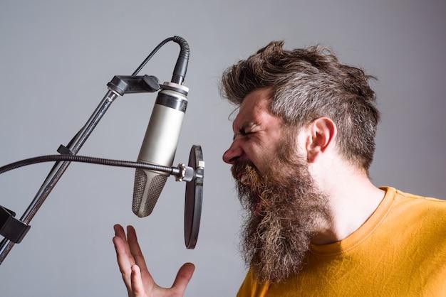 Brodaty mężczyzna w karaoke mężczyzna śpiewa z mikrofonem śpiewa w mikrofonie studyjnym śpiewa piosenkę