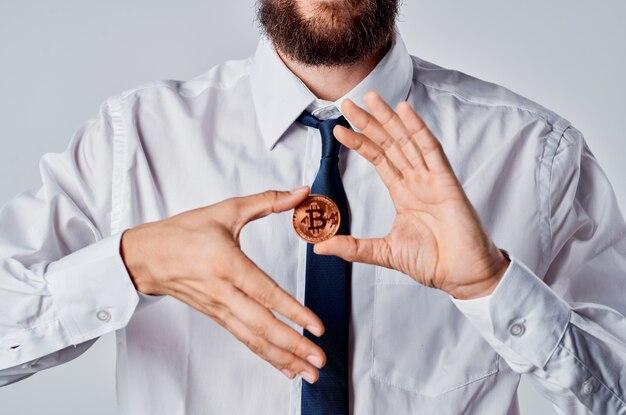 Brodaty mężczyzna w koszuli kryptowaluta trzymająca bitcoin w postaci monety