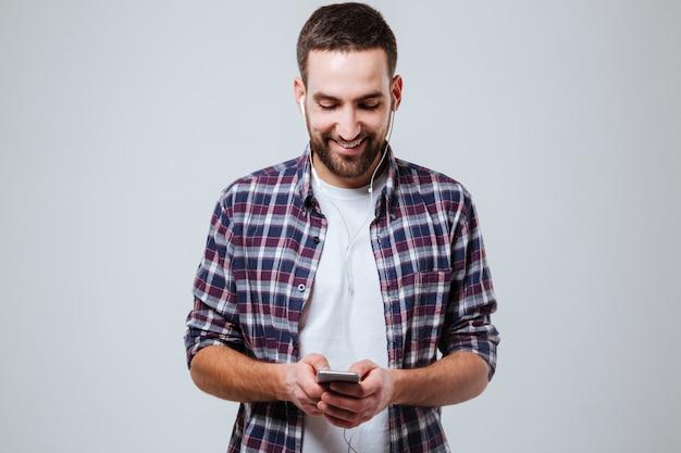 Brodaty mężczyzna w koszuli za pomocą smartfona