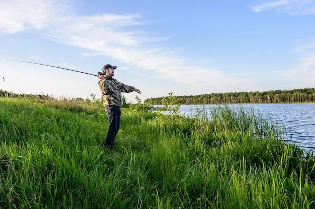 Brodaty mężczyzna w niebieskiej czapce z daszkiem na rzece rzuca spinningiem