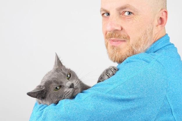 Brodaty mężczyzna w niebieskiej kurtce trzymający szarego kota