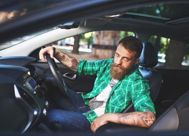Brodaty mężczyzna w nowym samochodzie.