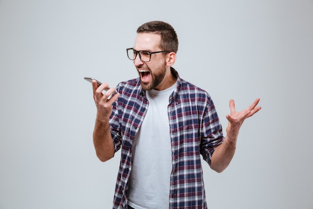 Brodaty mężczyzna w oczach krzyczy w telefonie