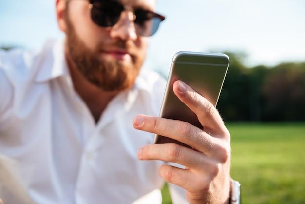 Brodaty mężczyzna w okularach przeciwsłonecznych i koszuli podczas korzystania ze smartfona. skoncentruj się na telefonie
