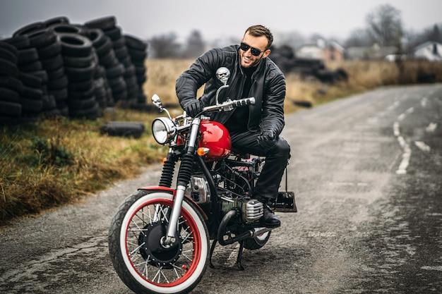 Brodaty mężczyzna w okularach przeciwsłonecznych i skórzanej kurtce ono uśmiecha się podczas gdy siedzący na czerwonym motocyklu na drodze.