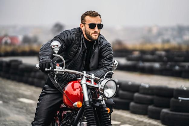 Brodaty mężczyzna w okularach przeciwsłonecznych i skórzanej kurtce siedzi na motocyklu na drodze.