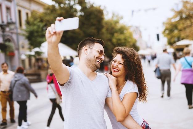 Brodaty mężczyzna w okularach przeciwsłonecznych przy selfie z piękną dziewczyną z kręconymi włosami.